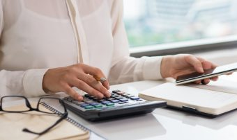 fechar-se-da-mulher-usando-calculadora-e-telefone-inteligente